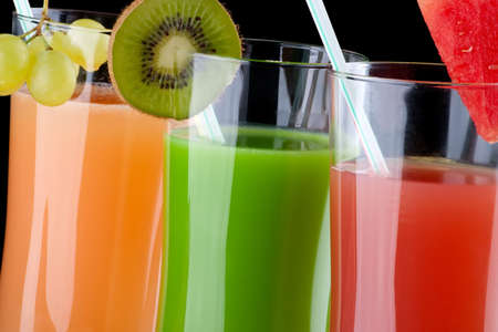 vertica: Three glasses of organic juice made from fresh fruits and surrounded by fresh ones. Series about organic and healthy drinks.