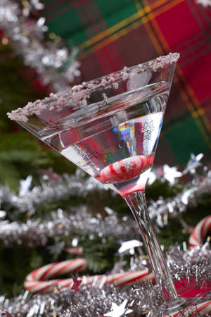 Closeup of glass of Candy Cane Martini and Christmas ornaments photo