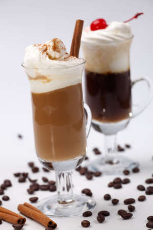 Two glasses of tasty Coffee Cocktails with whipped cream and maraschino cherry - Coffee Warmers series photo