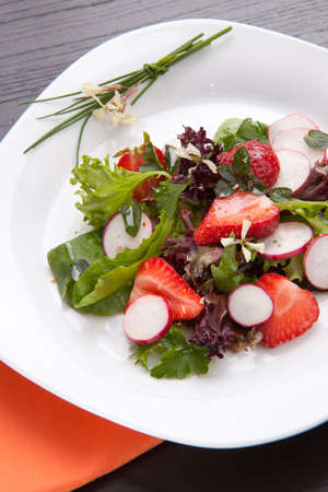 Plate of spring mix salad with radish, strawberry and chives photo