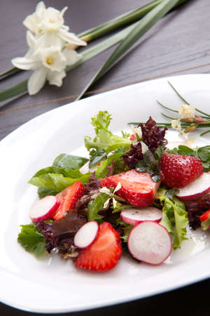 Closeup of plate of spring mix salad with radish, strawberry and chives. White daffodils in background photo