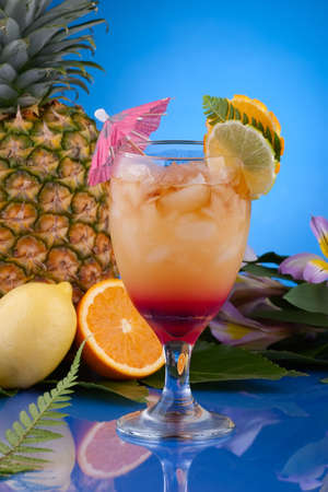 Mai Tai cocktail surrounded by tropical fruits. Rum, pineapple, orange juice garnished with slice of orange and lime. Most popular cocktails series. photo