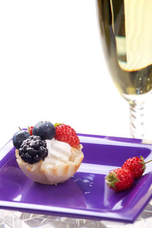Closeup of delicious fresh berry cake and glass of champagne 写真素材