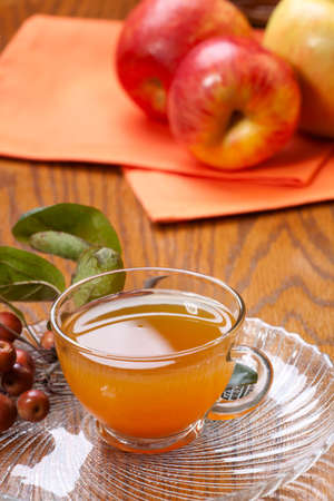 Closeup of glass of fresh pressed sweet cider and apples crop photo