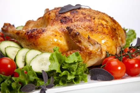 Whole roasted chicken garnished with fresh cucumbers, wine tomatoes, green salad and sage  Stock Photo