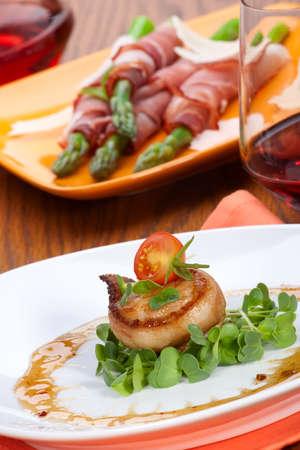 Close-up van Ginger soja Scallops verpakt met spek, gegarneerd met verse cherrytomaatjes en daikon spruiten.