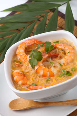 Closeup of bowl of Prawn Laksa soup with rice noodles, shrimps garnished with fresh cilantro. Stock Photo