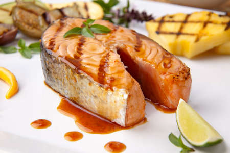 Delicious grilled Teriyaki salmon steak  garnished with grilled pineapple, baby eggplants, zucchini and chilli pepper for healthy style dinner. Stock Photo - 6302126
