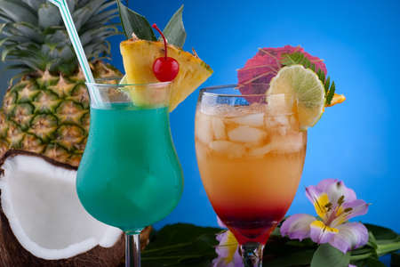 Closeup of Mai Tai and Blue Hawaiian cocktails surrounded by tropical fruits. Most popular cocktails series.