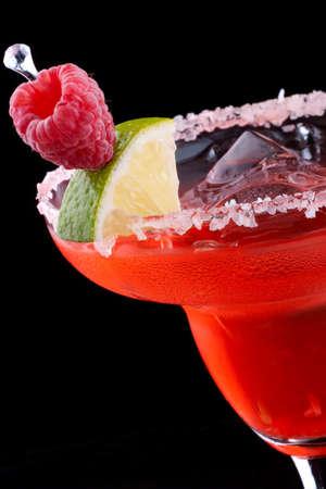 margarita cocktail: Margarita lampone in vetro refrigerata su sfondo nero sulla superficie di riflessione, guarnito con lamponi freschi e fetta di calce. Serie di cocktail pi� popolari. Archivio Fotografico