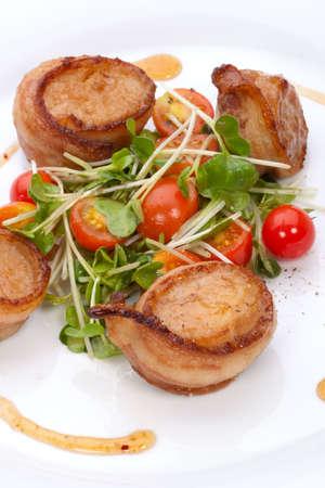 Closeup van Ginger soja Scallops omsloten door spek gegarneerd met verse cherry tomaten en rammenas bestaan.