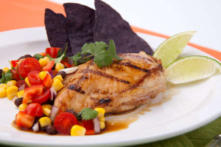Grilled chicken breast with salsa - black beans, corn, tomatoes, chilli pepper, cilantro, red onion - with  blue corn tortilla chips. photo