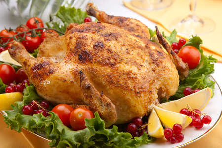 garnished: Whole roasted chicken garnished with fresh cucumbers, wine tomatoes, green salad and sage on dinner table Stock Photo