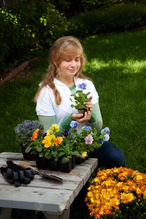Teenage girl is planting flowers in her backyard garden photo