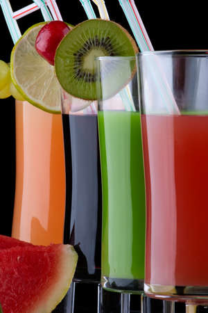 Glasses of organic juice made from fresh fruits and surrounded by fresh ones. Series about organic and healthy drinks. photo