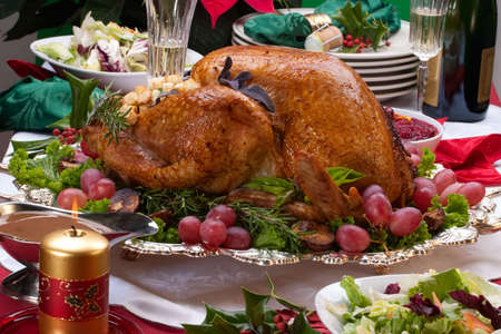 Garnished roasted turkey on Christmas decorated table with candles and flutes of champagne Stock Photo - 6539711