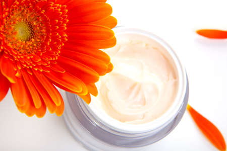 cremas faciales: Detalle de la jarra de hidrataci�n de la crema facial, rodeado de flores de gerberas naranja