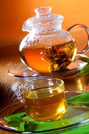 tea hot drink: Glass of greean tea and teapot with Chinese green tea. Jasmine flower inside. Stock Photo
