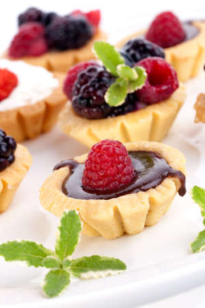 tart: Full tray of delicious fresh berry cakes garnished with pineapple mint
