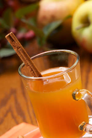 Closeup of glass of fresh pressed sweet cider, cinnamon sticks and apples crop photo