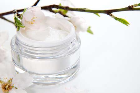cremas faciales: Detalle de la jarra de hidrataci�n de la crema facial, rodeado de flores de almendras