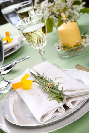 Daffodil table settings. Arrangements with yellow daffodil and fresh rosemary photo