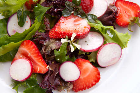 Closeup of plate of spring mix salad with radish, strawberry and chives. White daffodils in background Stock Photo - 6847247