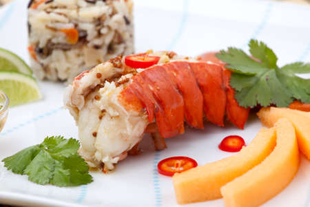 lobster tail: Closeup of delicious lobster tails served with spicy sauce, rice and melon