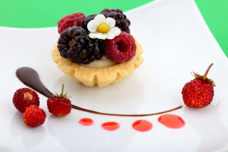 Closeup of delicious berry cake garnished with fresh wild strawberries