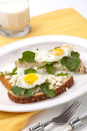 Nahaufnahme der köstlichen Open-Face Sandwiches mit Feta-Käse, Rucola und gebratenen Wachteleier.