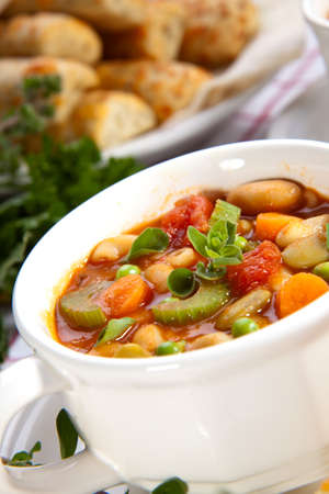 Two bowls of hot fresh Minestrone soup and cheese garlic breadsticks photo