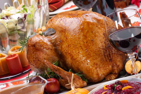 Garnished roasted turkey on holiday decorated table with pumpkins and glasses of red wine Stock Photo - 6951620