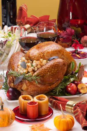 Garnished roasted turkey on holiday decorated table with pumpkins and glasses of red wine Stock Photo - 6951619