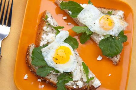 Closeup of delicious open-face sandwiches with feta cheese, arugula, and fried quail eggs.