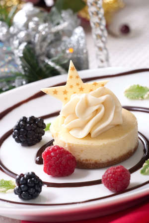 Delicious Vanilla Bean Cheesecake served with fresh blackberries and mint. Christmas ornament out of focus in background