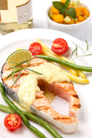 Closeup of delicious grilled salmon steak with tarragon sauce garnished with beans and cherry tomatoes. photo