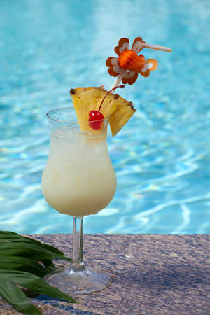 Glass of Pina Colada cocktail on swimming pool side photo