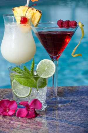 colada: Pina Colada, Mojito and Cosmopolitan cocktails on swimming pool side