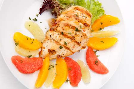 Pechuga de pollo a la plancha con ensalada de cítrico - pomelo rosa, limón, naranja, lechuga y tomillo fresco.  Foto de archivo - 7224401