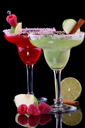 margarita cocktail: Apple e margaritas Raspberry in vetro refrigerata su sfondo nero sulla superficie di riflessione, guarnito fetta di mela verde, lamponi freschi, fetta di calce e stecca di cannella. Serie di cocktail pi� popolari.