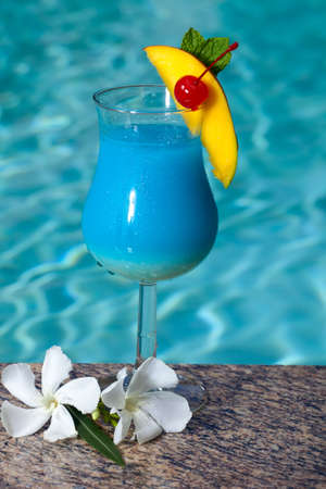 Glass of Blue Hawaiian cocktail on swimming pool side garnished with mango wedge and maraschino cherry photo