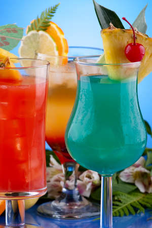 Mai Tai, Blue Hawaiian and Hurricane cocktails surrounded by tropical fruits. Most popular cocktails series. photo