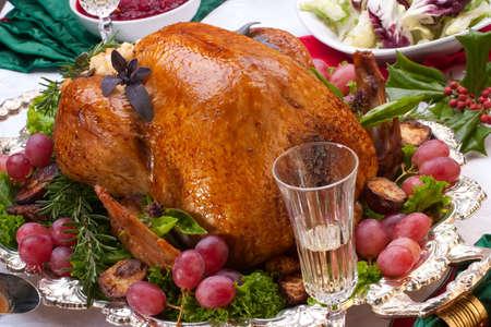 クリスマスに七面鳥の丸焼き添えて装飾キャンドルとシャンパンのフルートを持つテーブル 写真素材