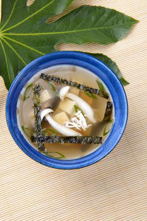 Closeup of bowl of miso soup with mushrooms, seaweeds and tofu. photo
