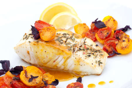 Pan fried halibut garnished with fennel seeds and spicy mustard sauce, served with fried cherry tomatoes salad with purple basil Banque d'images