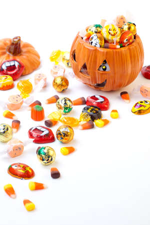 Scatter Halloween candies and orange pumpkin filled by them photo