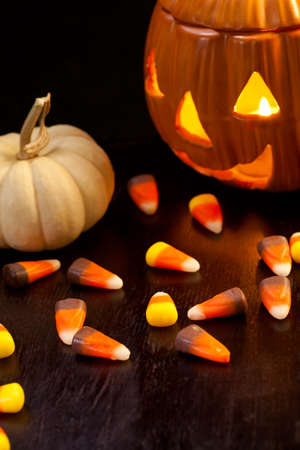 Scatter Halloween candies and orange pumpkin with light photo