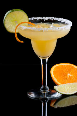 Orange Margarita in chilled glass over black background on reflection surface, garnished with fresh lime and orange. Most popular cocktails series. Stok Fotoğraf