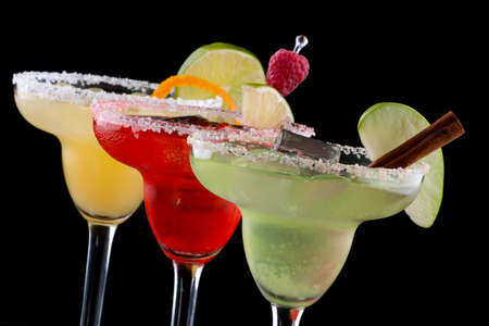 Three Margaritas - apple, orange and raspberry - in chilled glasses over black background, garnished with slice of green apple, limes, orange twist, raspberry and cinnamon stick. Most popular cocktails series. 版權商用圖片