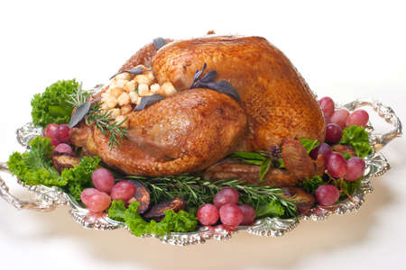 Garnished roasted turkey on platter over white background  photo